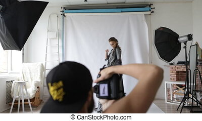 fashion model girl poses for the photographer in studio