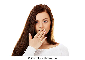 Young woman giggles covering her mouth with hand