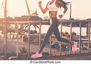 Keep running. Cropped image of beautiful young woman in sports clothing running along the bridge