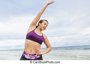 Young fit female stretching and heating up before outdoor...