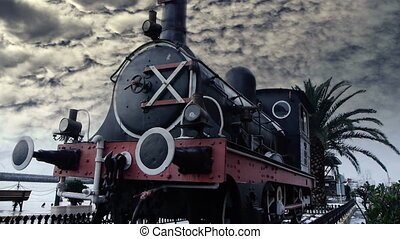 Historic steam engine with palm tree in background - History...