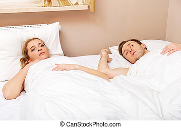 Young offended couple lying in bed