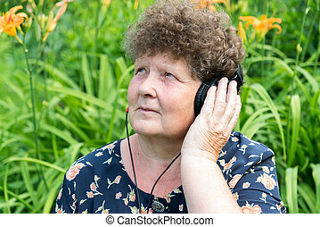 Curly woman listening to music with headphones - Curly woman...