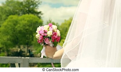 wedding bouquet of flowers in hands of the bride on green background