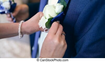 Bride putting on flower boutonniere on groom in black suit...