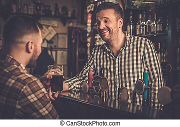 Handsome bartender talking with customer at bar counter in a...