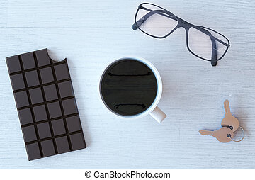 Coffee, chocolate and glasses - Topview of wooden desktop...