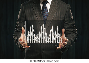 Businessman holding abstract business graph on dark...