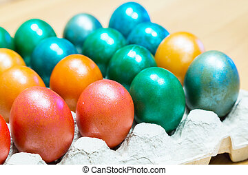 Colored Easter eggs in egg carton holder - Brightly colored...