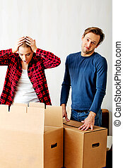 Couple unpaking boxes, woman looking to inside and aghast...