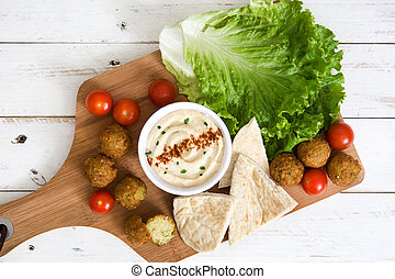 Healthy falafel with hummus on white wood
