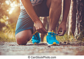 Runner tying shoelaces on sneakers Morning jogging in the...