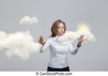 Young woman and sun shining out from behind the clouds,...