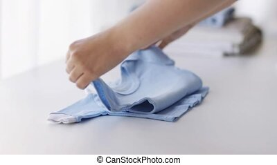woman hands folding baby boys clothes at home 12 -...