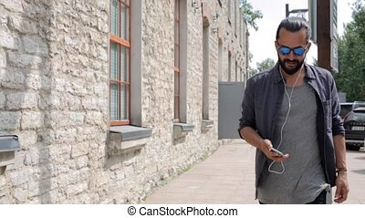 happy man with earphones over walking in city - people,...