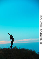 The silhouette of young woman is practicing yoga -...