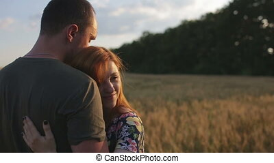 A couple hug, kiss and then walk in a wide open golden field...