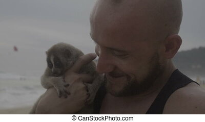 Man feeding slow loris on the beach - Handsome man holding...