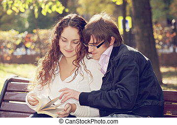 Couple reading book - Caucasian couple reading book while...