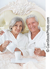 Senior couple in bed with coffee - happy Senior couple in...