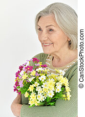 Senior woman with blooming flowers - Portrait of a senior...