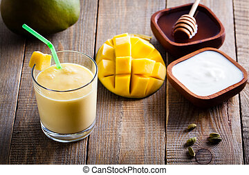 Glass of Indian drink made from yogurt with blended mango...