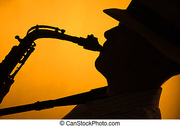 Silhouette of Sax Performer - A saxophone player with a hat...