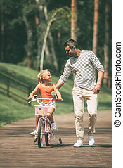 You can do it! Full length of cheerful father teaching his daughter to ride a bicycle in park