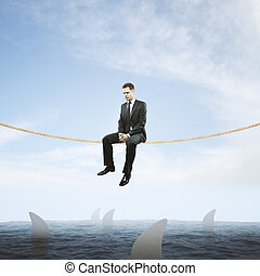 Man on rope above sharks - Risk concept with thoughtful...