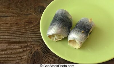 Fish rolls with sour herring on green plate