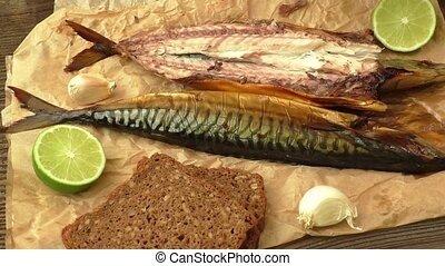 Whole smoked fish (mackerel) on a dark wooden table