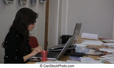 Woman with glasses working at a desk using a laptop.