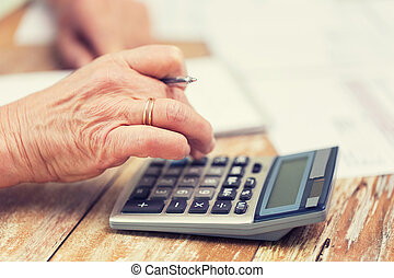 close up of senior woman counting with calculator -...