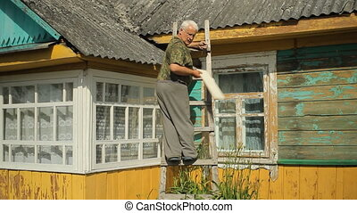A man tries to fix the roof. He is standing on the stairs near the house
