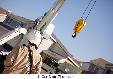 Utility Worker Navigating Remote Crane - Utility Worker with...