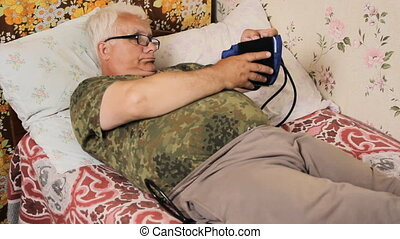 Senior man lying on the bed and measures the blood pressure...