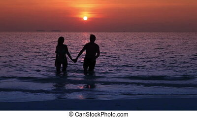 Silhouettes of the man and woman, leaving the sea at sunset