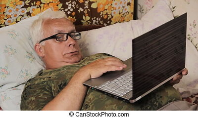 Senior man in the bed at home with laptop. Laptop on his stomach