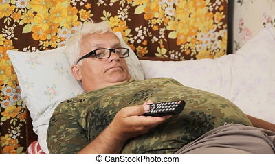 Senior man in the bed at home with TV remote control