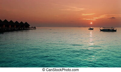 Houses over the sea at sunrise Maldives ,