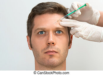 Handsome man is getting injection. Concept of aesthetic...