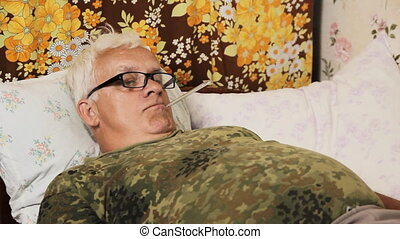 Senior man sick in bed with a thermometer in his mouth at home