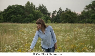 The girl in the meadow gathering bouquet of wildflowers