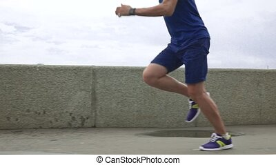 Man in blue clothes running on embankment after rain and stepping into pool. Super slow motion steadicam shot at 240 fps