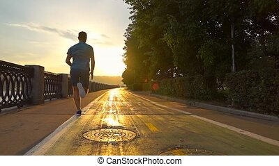 Man in blue uniform running on summer sunset embankment...