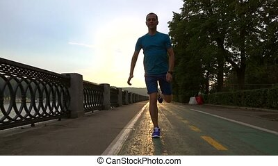 Runner in blue clothes running at the camera along summer sunset embankment of Moscow river.