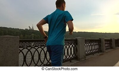 Athletic man in blue uniform runs from the camera along summer sunset embankment of Moscow river. Slow motion steadicam shot at 120 fps