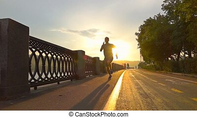 Sportsman in blue uniform running on summer sunset embankment along bicycle road, Moscow. Super slow motion steadicam shot at 240 fps