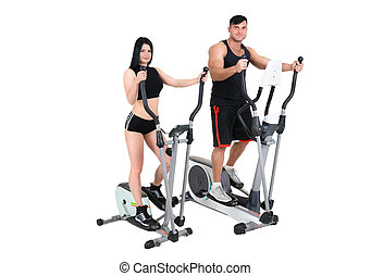 young woman and man doing exercises on elliptical cross...