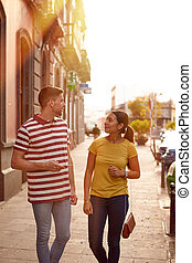 Cute young couple walking down a sidewalk - Young couple...